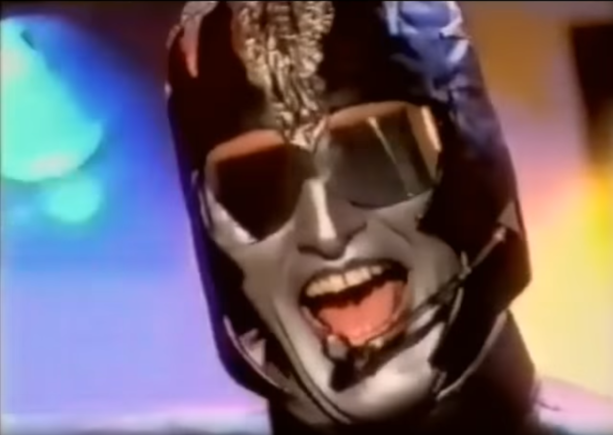 screencap of music video performer in futuristic costume silver facepaint.